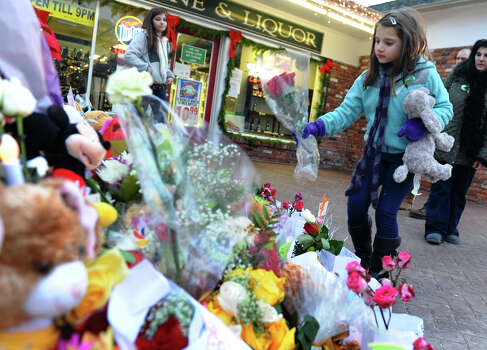 Eight year old Samantha DelGiudice, a third grader at Sandy Hook Elementary School, places some flowers and a stuffed animal at a memorial for victims from last Friday's shooting massacre at the school in Newtown, Conn. on Thursday December 20, 2012. Photo: Christian Abraham / Connecticut Post