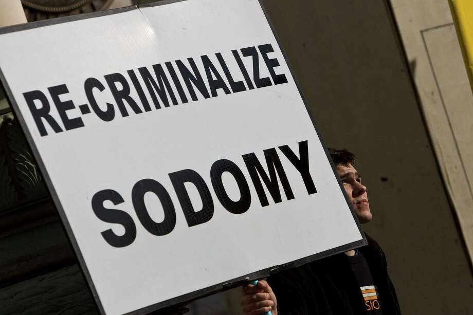 "Dennis Choban looks up while he holds a sign saying ""Re-Criminalize Sodomy"" while supporters and opponents to same sex marriage protest in San Francisco, California. Photo: David Paul Morris, Getty Images / 2008 Getty Images"