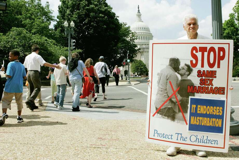 Tourists walk past Joseph Deazevedo (R) of Utah while he holds a sign protesting against same sex marriage on Capitol Hill in Washington D.C. Photo: Mark Wilson, Getty Images / 2006 Getty Images