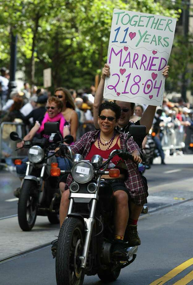 "A couple riding with the group ""dykes on bikes"" carries a sign in San Francisco. Photo: Justin Sullivan, Getty Images / 2004 Getty Images"