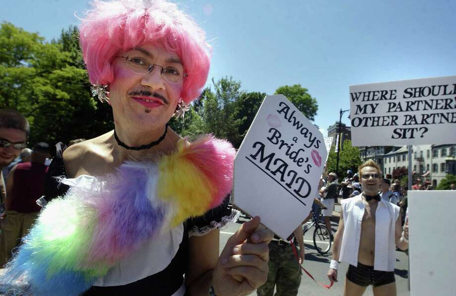 A parade goer holds aloft a sign on during the Boston Gay Pride Parade in Boston, Mass. Photo: Darren McCollester, Getty Images / 2004 Getty Images
