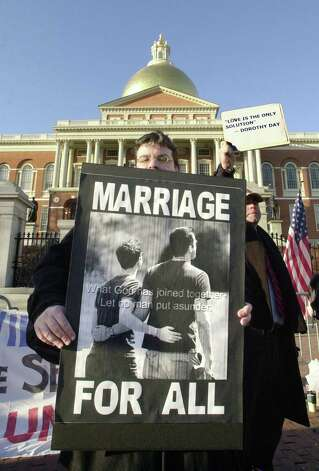 A supporter of gay marriage holds a sign outside the Massachusetts State House, where the Legislature was in its second day of debate over a possible constitutional amendment banning same-sex marriage in Boston, Mass. Photo: Michael Springer, Getty Images / 2004 Getty Images