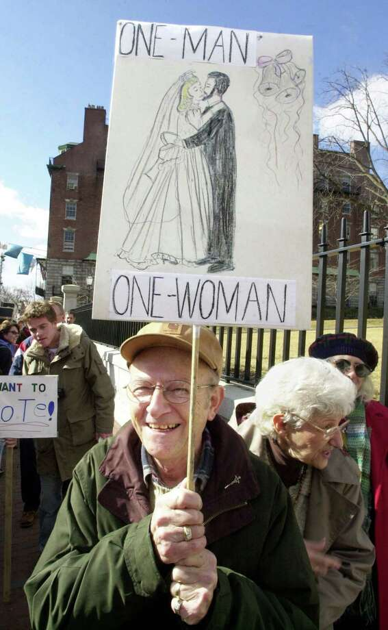 A man in opposed to gay marriage carries a sign in front of the State House as the Legislature inside prepared to convene a Constitutional Convention to consider a proposed amendment defining marriage as a union between a man and a woman in Boston, Mass. Photo: Michael Springer, Getty Images / 2004 Getty Images