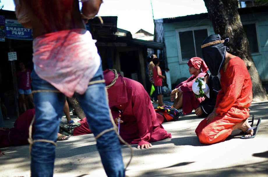 Flagellants whip their backs with wooden flails during holy week on March 28, 2013 in Pampanga province, Philippines. Flagellation (Penitensya in Filipino) is an extreme act of mortification in which the penitent scourges himself by whipping his own flesh. Although the blody practice is condemned by the Catholic church and frowned upon in the modern age, hundreds of Filipino faithfuls still practice it to this day as a form of panata, or vow, and has become a part of Philippine culture and tradition. Photo: Dondi Tawatao, Getty Images / 2013 Dondi Tawatao