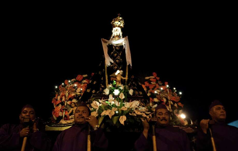 """Penitents walk with the statue of """"The Dolorous"""" during the procession of the Holy Wednesday in Cali, Valle del Cauca department, Colombia, on March 27, 2013. Photo: Getty Images"""