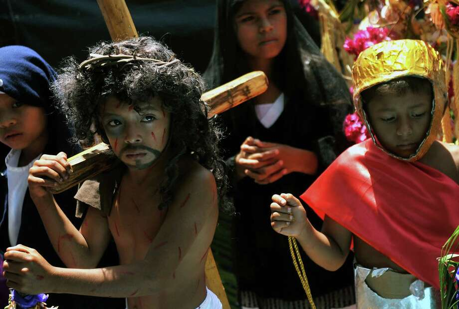 Children reenact the crucifixion of Jesus during an aquatic Via Crucis carried out on boats between the islets of the Nicaragua -Cocibolca- lake, in Granada, on March 27, 2013.  AFP PHOTO/Hector RETAMAL Photo: AFP, Getty Images / 2013 AFP