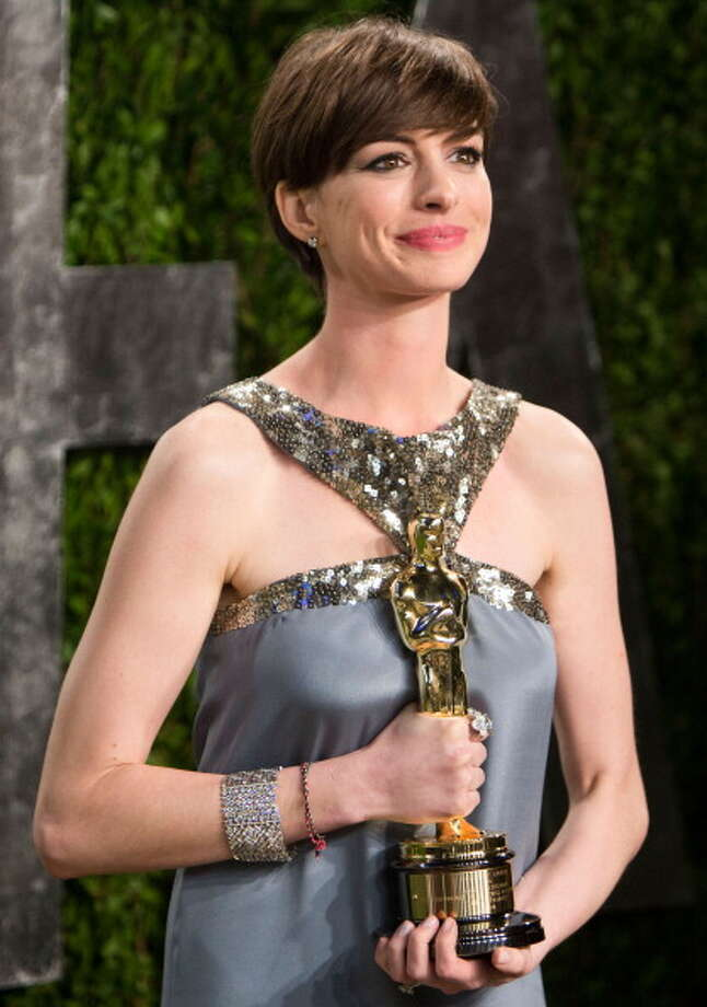 Anne Hathaway carrying her Oscar for best supporting actress at the Vanity Fair Oscar Party. Mission accomplished. Photo: ADRIAN SANCHEZ-GONZALEZ, AFP/Getty Images / 2013 AFP