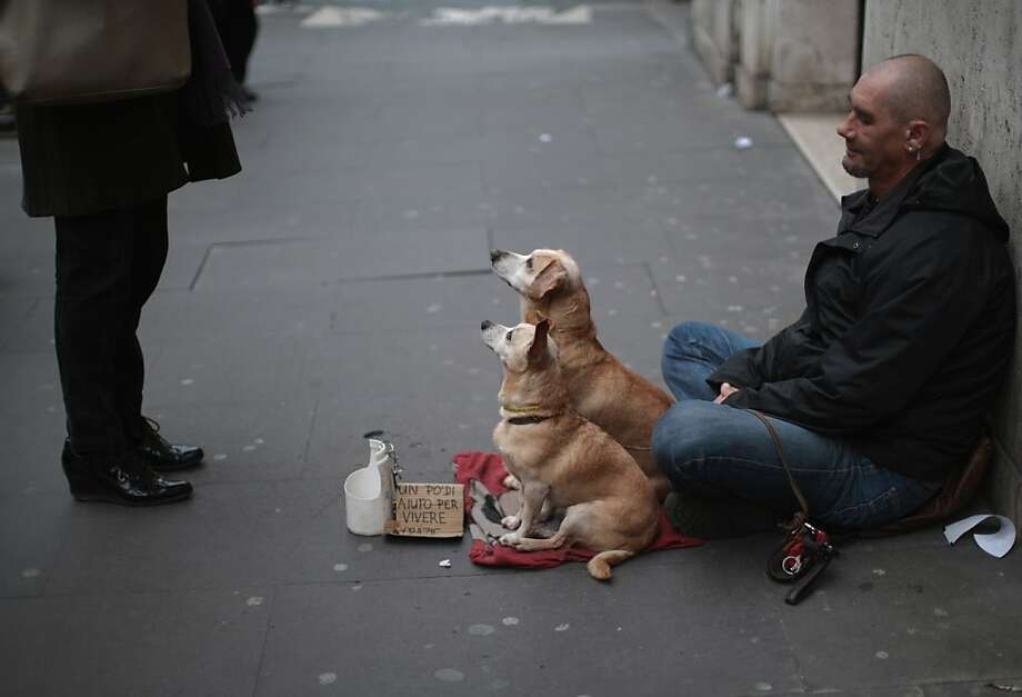 "We also accept meatballs:A man and his dogs ""beg for loose change"" in a street in Rome. Photo: Christopher Furlong, Getty Images"