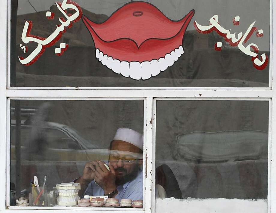 The palates of fine art: An Afghan dentist crafts dentures in his storefront shop in Kandahar,  Afghanistan. Photo: Allauddin Khan, Associated Press