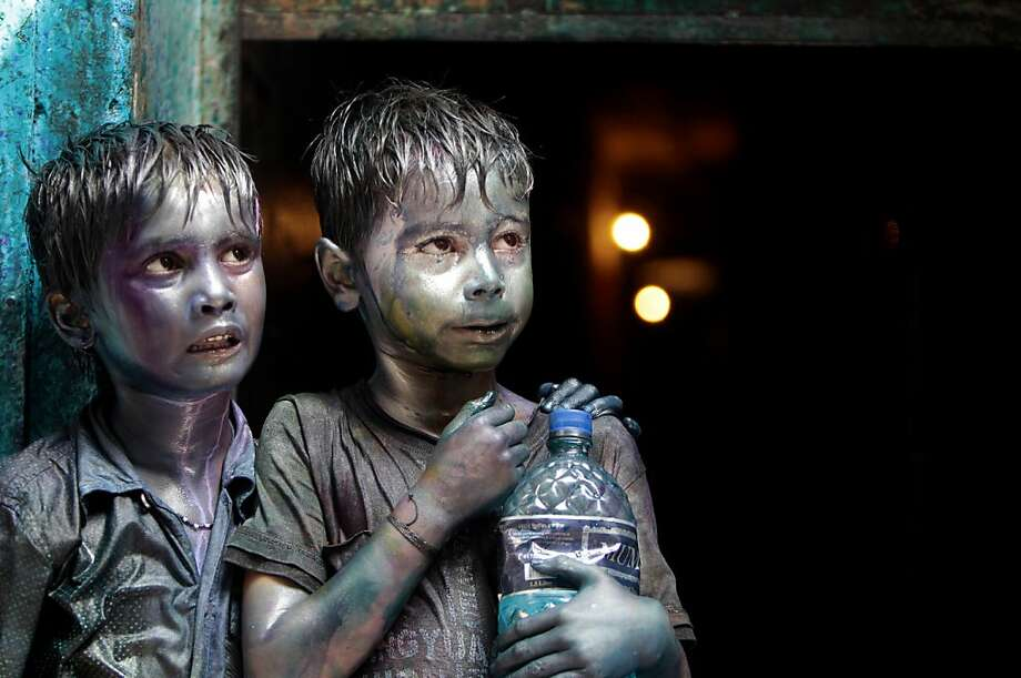 Bangladeshi Hindu children smeared in colors stand at a doorway as they watch Holi festival celebrations in Dhaka, Bangladesh, Thursday, March 28, 2013. Hindus celebrate Holi, the festival of colors, by painting each other in bright pigments, distributing sweets and squirting water at one another. The holiday celebrated mainly in India and Nepal marks the beginning of spring and the triumph of good over evil.   (AP Photo/A.M. Ahad) Photo: A.M. Ahad, Associated Press