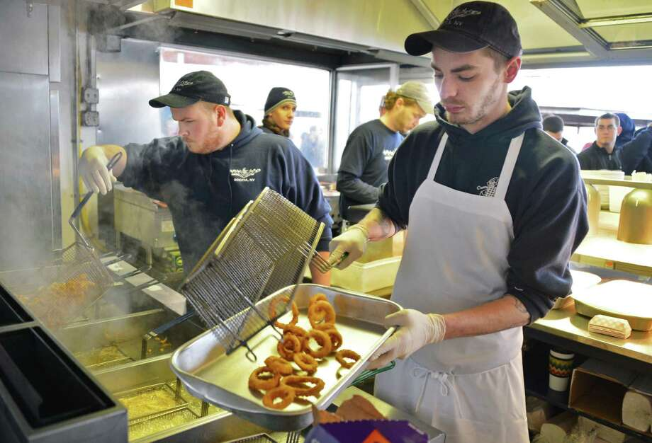 Employees John Lenkewich, left, and Rich Mourer work to keep up with lines of customers as Jumpin' Jack's Drive-In in Scotia opens for the season Thursday March 28, 2013.  (John Carl D'Annibale / Times Union) Photo: John Carl D'Annibale / 10021452A