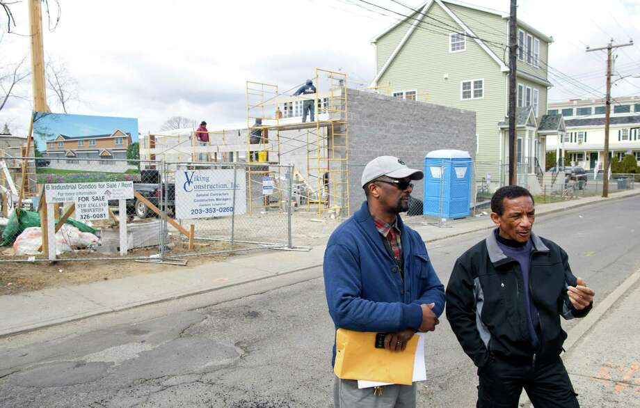 "John Wooten, left, and his neighbor Bob Owens, right, talk in front of a construction site where signs advertise six ""industrial condos"" will be for sale or rent in their residential neighborhood on Cedar Street in Stamford on Thursday, March 28, 2013. Photo: Lindsay Perry / Stamford Advocate"