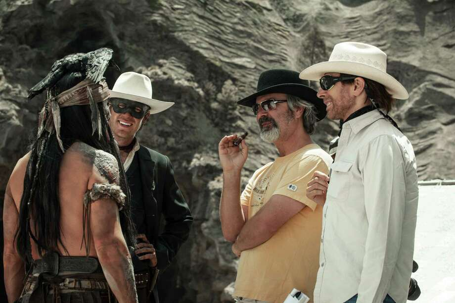 """This undated publicity photo released by Disney/Bruckheimer Films shows, from left, Johnny Depp as Tonto, Armie Hammer as The Lone Ranger, director, Gore Verbinski and producer, Jerry Bruckheimer, on the set of """"The Lone Ranger."""" The film opens nationwide on July 3, 2013. (AP Photo/Disney/Bruckheimer Films, Peter Mountain) Photo: Peter Mountain"""