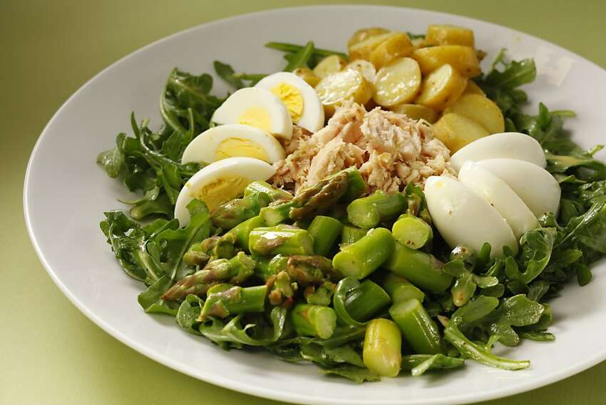 A spring version of the French classic Salade Nicoise subs asparagus spears for green beans and leaves out tomatoes. Plate it as a composed salad, arranging each ingredient atop a bed of dressed arugula.