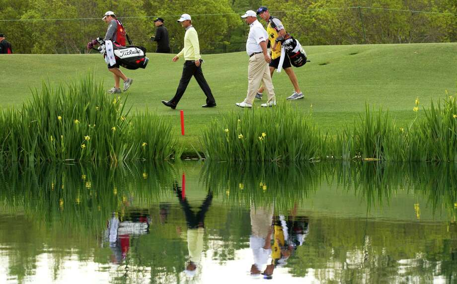 Brendon de Jonge, yellow, and Matt Jones, in white shirt, are reflected in the water as they walk up the 18th fairway. Photo: Brett Coomer, Houston Chronicle / © 2013 Houston Chronicle
