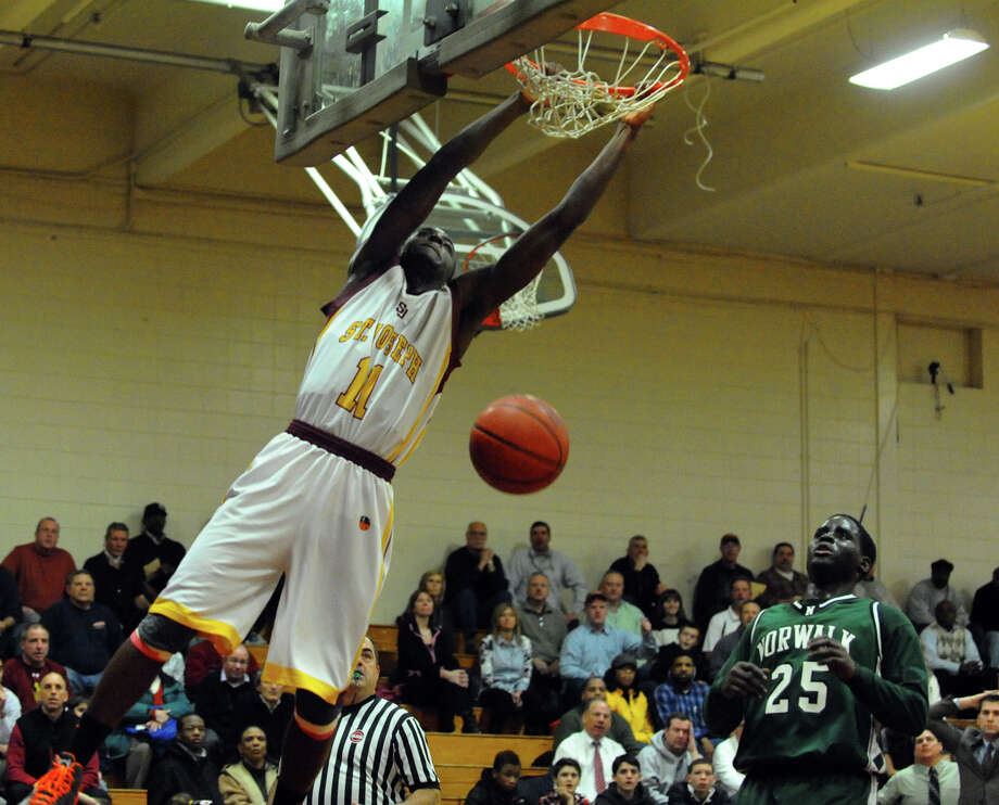 St. Joseph's #11 Quincy McKnight slam dunks the ball, during boys basketball action against Norwalk in Trumbull, Conn. on Tuesday February 2, 2013. Photo: Christian Abraham / Connecticut Post