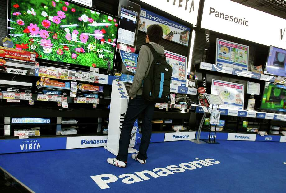 A shopper looks at a Panasonic flat-panel television at an electronics retail store in Tokyo Thursday, March 28, 2013. Panasonic Corp.'s president said Thursday the company will get out of unprofitable businesses but stopped short of ditching the Japanese manufacturer's money-losing TV operations, as had been widely speculated. (AP Photo/Shizuo Kambayashi) Photo: Shizuo Kambayashi