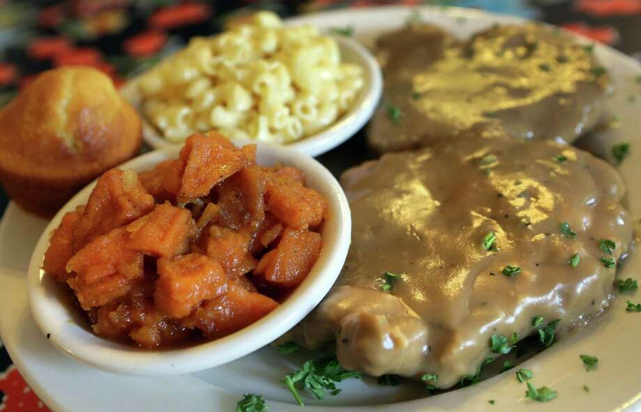 Smothered pork chops with yams, mac and cheese and a corn bread muffin. Just try to resist. Photo: Photos By Bob Owen / San Antonio Express-News