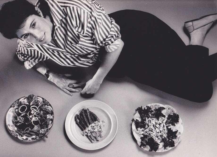 Deborah Madison lies down next to some salads, 1988