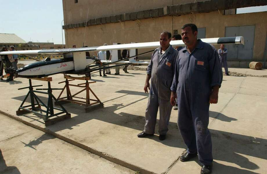 "Iraqi officials show off their 7.45-meter-wingspan Remotely Piloted Vehicle 30A, or the ""Jerusalem 10,"" to members of the news media on March 12, 2003 in Baghdad. Iraq declared the drone in a January 15, 2003 report, but with a 4.4-meter wingspan, an error that Iraqis say was a ""typing mistake."" Though the drone looked like a science project, with tin foil and duct tape holding it together, U.S. officials building a case for war called it a ""smoking gun."" Photo: Scott Peterson, Getty Images / Scott Peterson"