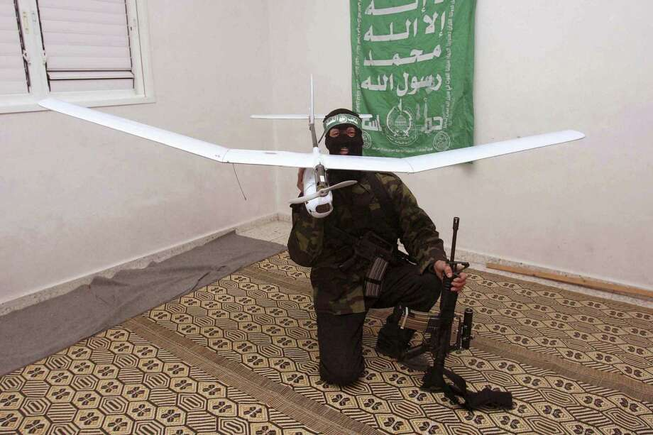 In this handout photo released by the Hamas media office January 11, 2007, a member of the Al-Qassam brigade, the military wing of Hamas Movement, poses with an Israeli spy drone which Hamas says was captured in the Gaza strip. Photo: Handout, Getty Images / 2007 Getty Images
