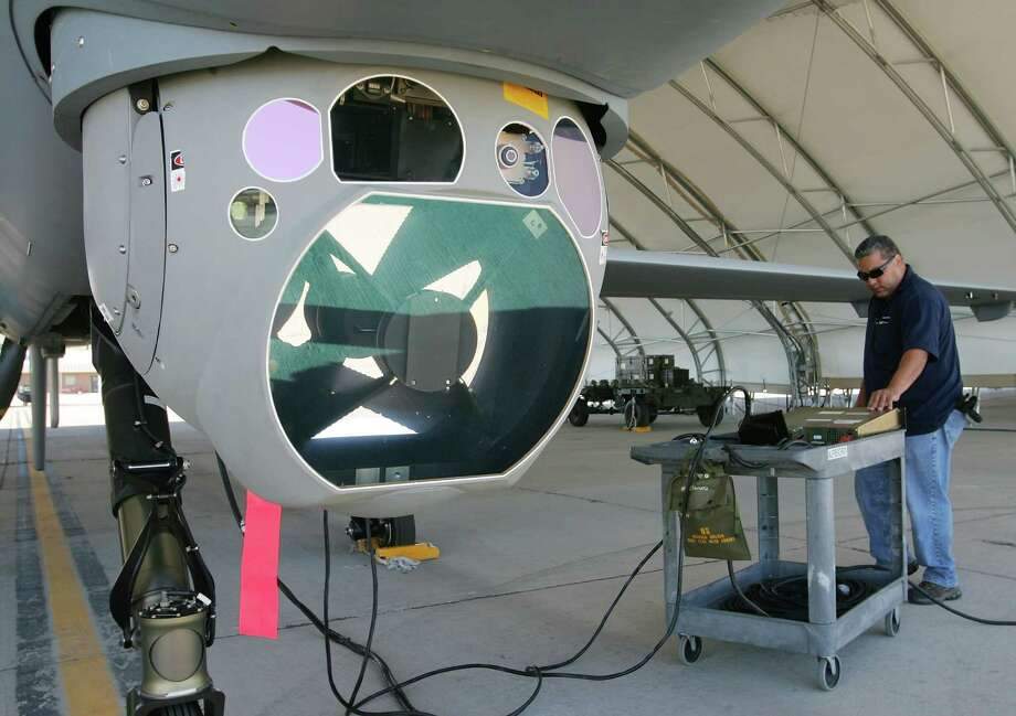 Michael Martinez, airframe and power plant mechanic with General Atomics Aeronautical Systems Inc., inspects an MQ-9 Reaper next to the aircraft's targeting pod during a pre-flight check August 8, 2007 at Creech Air Force Base in Indian Springs, Nev. Photo: Ethan Miller, Getty Images / 2007 Getty Images