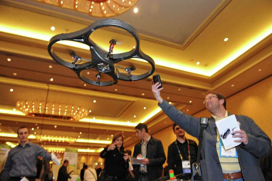 An attendee photographs an A.R. Drone helicopter by Parrot as it flies overhead during a press event for the 2010 International Consumer Electronics Show January 6, 2010 in Las Vegas. The device is controlled wirelessly from an iPhone. Photo: ROBYN BECK, AFP/Getty Images / 2010 AFP