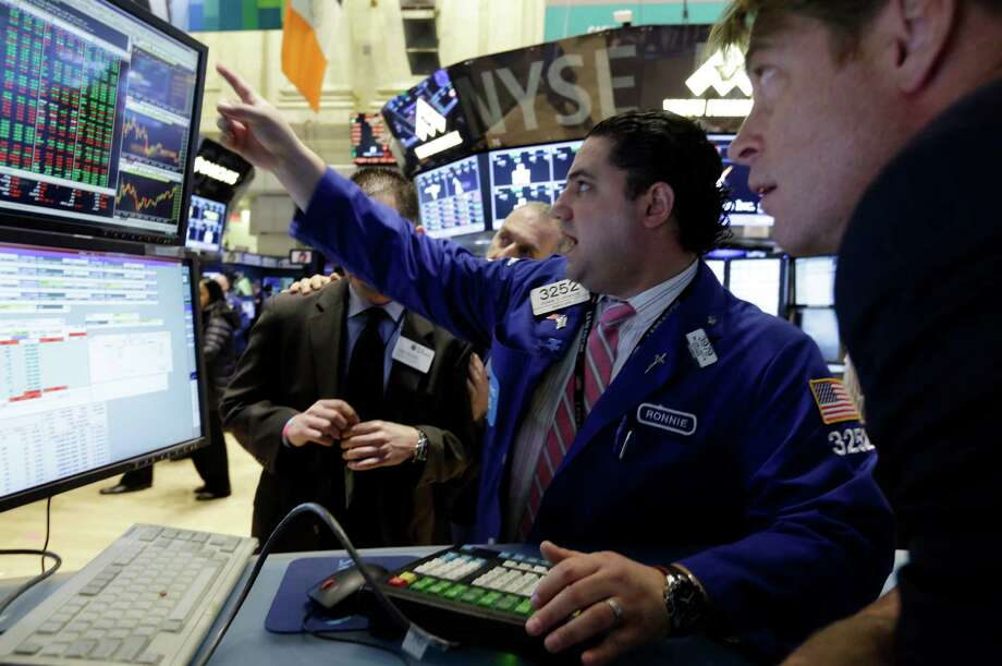 Specialist Ronnie Howard, center, works at his post on the floor of the New York Stock Exchange Thursday, March 28, 2013. The Standard & Poor's 500 index closed at a record high Thursday, beating the mark it set in October 2007. The S&P rose six points to 1,569, a gain of 0.4 percent, beating its previous record by four points. The index is still shy of its all-time trading high of 1,576. (AP Photo/Richard Drew) Photo: Richard Drew