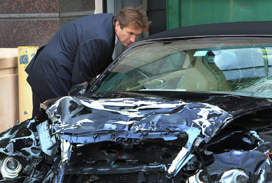 John Goodman looks over his wrecked Bentley, after jurors had finished looking at both cars involved in the deadly crash, entered as part of evidence during Goodman's  DUI Manslaughter trial  on Thursday, March, 15, 2012, in West Palm Beach, Fla.  Goodman is accused of driving drunk and leaving the scene of the February 2010 crash that killed 23-year-old Scott Wilson. (AP Photo/The Palm Beach Post, Lannis Waters, Pool) Photo: Associated Press / Pool, Palm Beach Post