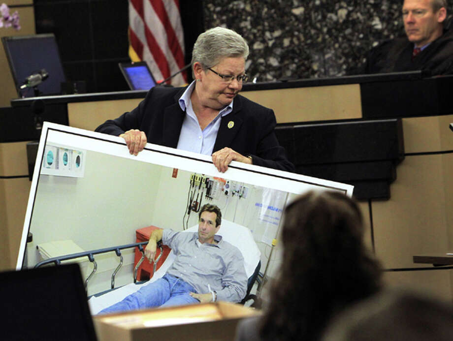 Prosecutor Ellen Roberts carries a photo of John Goodman taken in the hospital the night of the crash during John Goodman's DUI Manslaughter trial  on Thursday, March, 15, 2012, in West Palm Beach, Fla.  Goodman is accused of driving drunk and leaving the scene of the February 2010 crash that killed 23-year-old Scott Wilson. (AP Photo/The Palm Beach Post, Lannis Waters, Pool) Photo: Lannis Waters, Associated Press / Pool, Palm Beach Post
