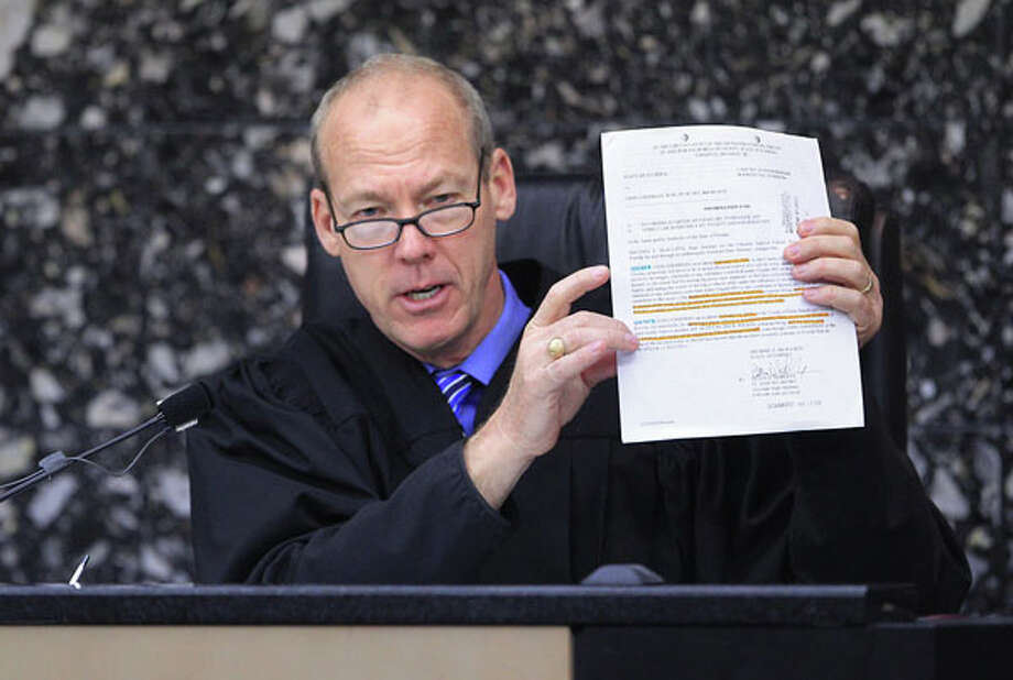 Judge Jeffrey Colbath holds up a court document during the second day of jury selection in John Goodman's DUI manslaughter trial in West Palm Beach, Fla., Wednesday, March 7, 2012. Goodman, the founder of the International Polo Club Palm Beach, is accused of driving drunk and leaving the scene of the February 2010 crash that killed 23-year-old Scott Wilson. (AP Photo/The Palm Beach Post, Lannis Waters, Pool) Photo: Lannis Waters, Associated Press / Palm Beach Post