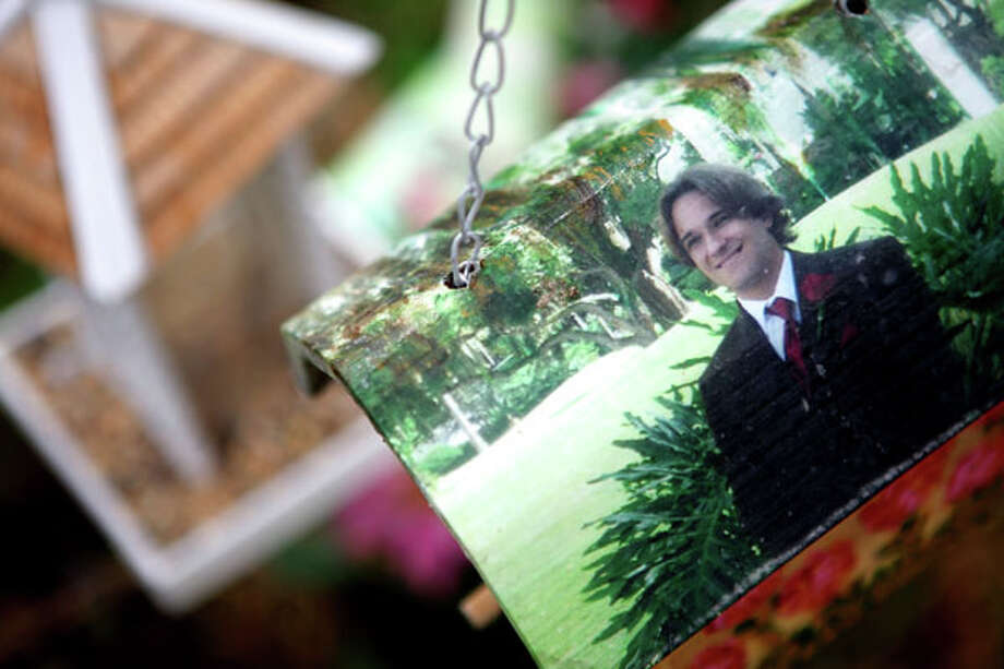 In a May 19, 2010 photo, a photo of Scott Wilson is attached to a bird house, part of a memorial next to the canal where he died in a car cash in Wellington, Fla. Wilson drowned after his car was allegedly hit and knocked into a canal by multimillionaire polo magnate John Goodman. A lawyer for Wilson's mother said in a court filing that Goodman's adoption of his 42-year-old girlfriend was meant to disguise his true wealth should he be found liable and forced to pay punitive damages. (AP Photo/Palm Beach Post, Brandon Kruse)  MAGS OUT; TV OUT; NO SALES Photo: Brandon Kruse, Associated Press / The Palm Beach Post