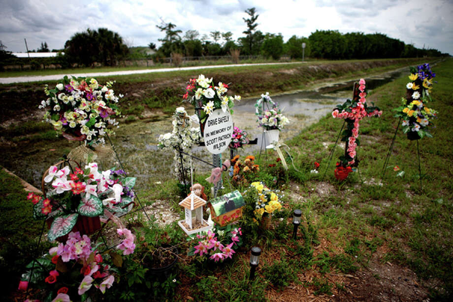 In a May 19, 2010 photo, a memorial is set up, for Scott Wilson at the canal where he died after a car crash, in Wellington, Fla. Wilson drowned after his car was allegedly hit and knocked into a canal by multimillionaire polo magnate John Goodman. A lawyer for Wilson's mother said in a court filing that Goodman's adoption of his 42-year-old girlfriend was meant to disguise his true wealth should he be found liable and forced to pay punitive damages. (AP Photo/Palm Beach Post, Brandon Kruse)  MAGS OUT; TV OUT; NO SALES Photo: Brandon Kruse, Associated Press / The Palm Beach Post
