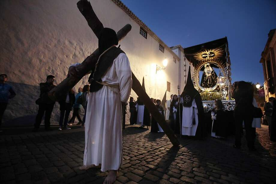 "The prisoner who will receive perdon today carries a cross as he takes part in a procession with penitents of the ""Nuestra Senora del Rosario"" brotherhood during the Holy Week in La Laguna on the Spanish Canary island of Tenerife on March 28, 2013.    AFP PHOTO/ DESIREE MARTINDESIREE MARTIN/AFP/Getty Images Photo: Desiree Martin, AFP/Getty Images"