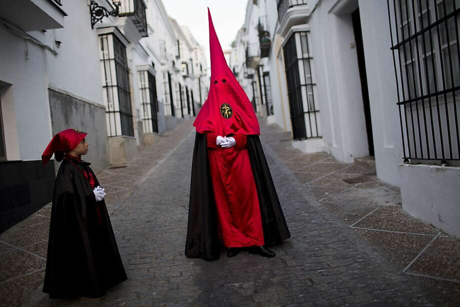 "Cristina from the ""Cristo de la Buena Muerte"" brotherhood poses for a photo on her way to the church to take part in a procession in Medina Sidonia village, in Cadiz province, Spain, Thursday, March 28, 2013. Hundreds of processions take place throughout Spain during the Easter Holy Week.  (AP Photo/Emilio Morenatti) Photo: Emilio Morenatti, Associated Press"
