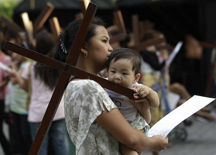 A Filipino child bites a wooden cross as devotees practice different religious rites during the Holy Week at the Philippine Center of Saint Pio of Pietrelcina on Thursday, March 28, 2013 in suburban Quezon city, east of Manila, Philippines.(AP Photo/Aaron Favila) Photo: Aaron Favila, Associated Press