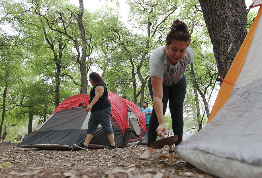 Desirey De Leon (right) secures a post on her tent while step-mother Amy Cancino and her father, John, were putting up their tent at Brackenridge Park on Thursday, Mar. 28, 2013. The family has celebrated Easter at the park for about four years. They finally settled on a spot near the river. Other campers were slowly making their arrival to the park either in person or by placing chained chairs near the spots they hope to spend Easter with family. The city officially lifted the overnight curfew so that campers can celebrate the holiday over the weekend without having to leave the park. Photo: Kin Man Hui, San Antonio Express-News / © 2012 San Antonio Express-News