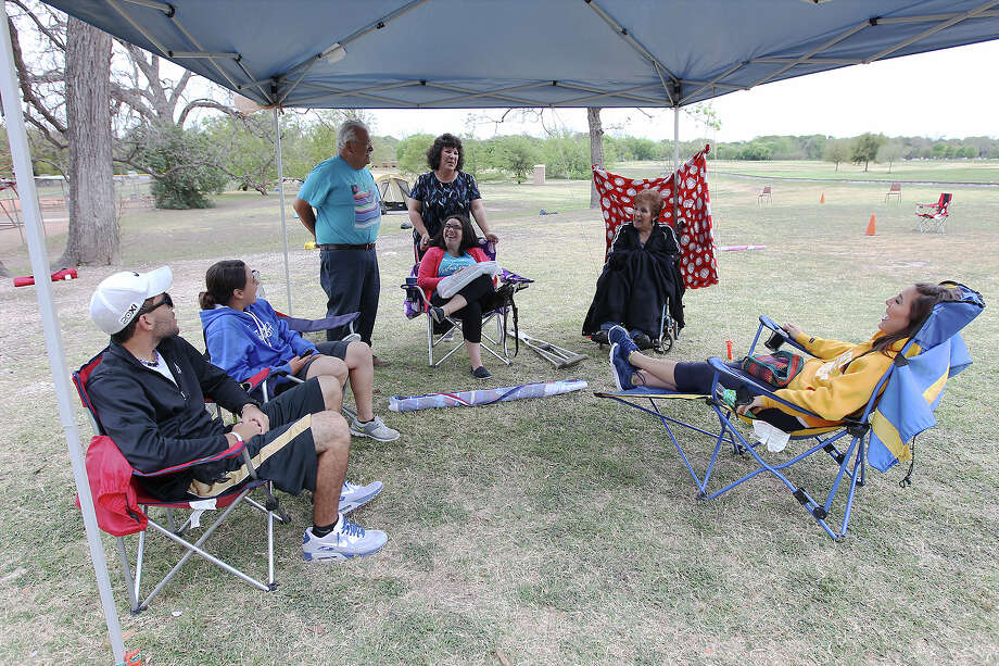 The Morales family gather to relax under a canopy at a spot they selected at Brackenridge Park on Thursday, Mar. 28, 2013. The Moraleses have celebrated Easter weekend at nearly the same spot for more than 30 years. They expect to have about 60 people at the camp site and plan to play softball and horseshoes along with enjoying barbecue. Photo: Kin Man Hui, San Antonio Express-News / © 2012 San Antonio Express-News