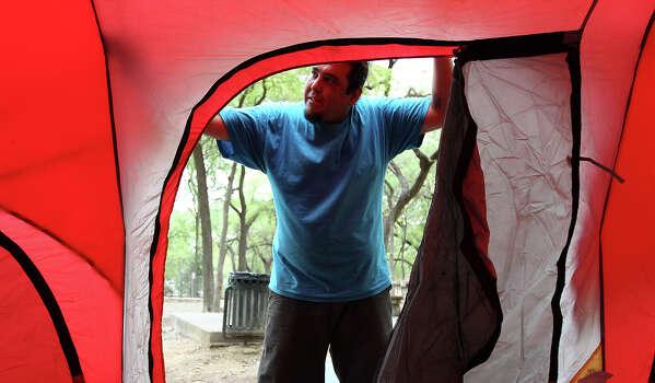 John De Leon finishes putting up his tent at Brackenridge Park on Thursday, Mar. 28, 2013.  Photo: Kin Man Hui, San Antonio Express-News / © 2012 San Antonio Express-News