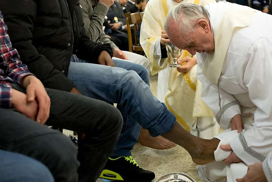 In this photo provided by the Vatican newspaper L'Osservatore Romano, Pope Francis washes the foot of an inmate at the juvenile detention center of Casal del Marmo, Rome, Thursday, March 28, 2013. Francis washed the feet of a dozen inmates at a juvenile detention center in a Holy Thursday ritual that he celebrated for years as archbishop and is continuing now that he is pope. Two of the 12 were young women, an unusual choice given that the rite re-enacts Jesus' washing of the feet of his male disciples. The Mass was held in the Casal del Marmo facility in Rome, where 46 young men and women currently are detained. Many of them are Gypsies or North African migrants, and the Vatican said the 12 selected for the rite weren't necessarily Catholic. (AP Photo/L'Osservatore Romano, ho) Photo: Associated Press