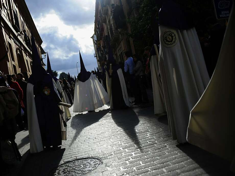 "Penitents of the ""Las Cigarreras"" brotherhood take part in a procession during the Holy Week in Sevilla on March 28, 2013. Christian believers around the world mark the Holy Week of Easter in celebration of the crucifixion and resurrection of Jesus Christ.     AFP PHOTO/ CRISTINA QUICLERCRISTINA QUICLER/AFP/Getty Images Photo: Cristina Quicler, AFP/Getty Images"