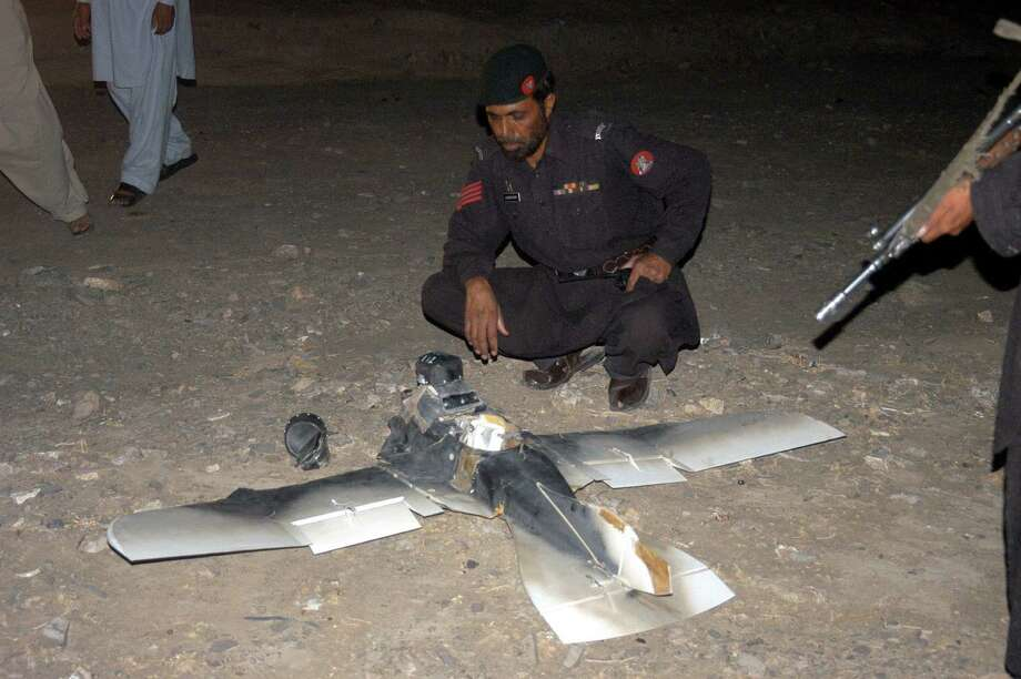 Pakistani security personnel examine a crashed American surveillance drone in Chaman, Pakistan on August 25, 2011.  The American surveillance drone crashed near a paramilitary base close to the Afghan border, Pakistani officials said. Photo: ASGHAR ACHAKZAI, AFP/Getty Images / 2011 AFP