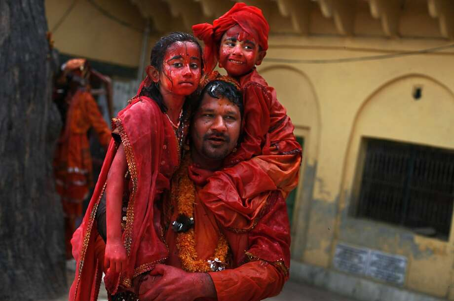 An Indian Hindu priest carries his children after the end of celebrations marking Holi, the Hindu festival of colors, at the Dauji Temple in Dauji, south of New Delhi, India, Thursday, March 28, 2013. The Dauji Temple festivities are known for a ritual where the women playfully hit men with whips made of cloth as men throw buckets of water with orange dye. (AP Photo/Altaf Qadri) Photo: Altaf Qadri, Associated Press