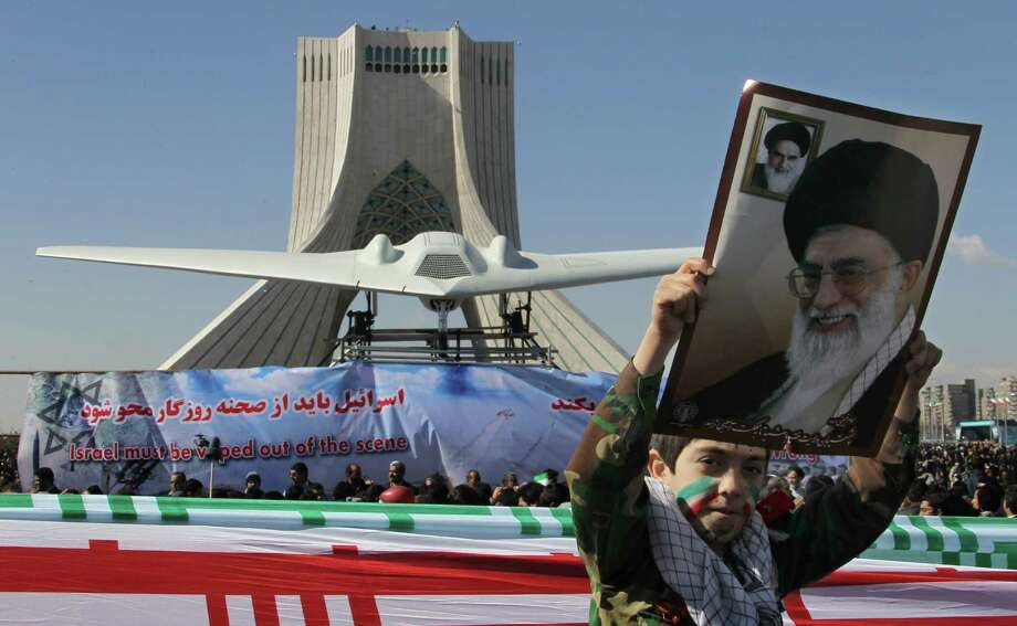 An Iranian boy holds a portrait of supreme leader, Ayatollah Ali khamenei as he walks past a replica of the captured U.S. RQ-170 drone on display next to the Azadi (Freedom) tower during the 33rd anniversary of the Islamic revolution in Tehran on February 11, 2012. Photo: ATTA KENARE, AFP/Getty Images / 2012 AFP