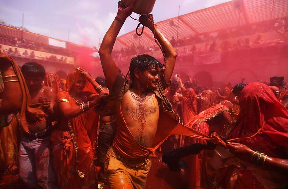 Indian Hindu women playfully tear the clothes of a man during celebrations marking Holi, the Hindu festival of colors, at the Dauji Temple in Dauji, south of New Delhi, India, Thursday, March 28, 2013. The Dauji Temple festivities are known for a ritual where the women playfully hit men with whips made of cloth as men throw buckets of water with orange dye. (AP Photo/Altaf Qadri) Photo: Altaf Qadri, Associated Press
