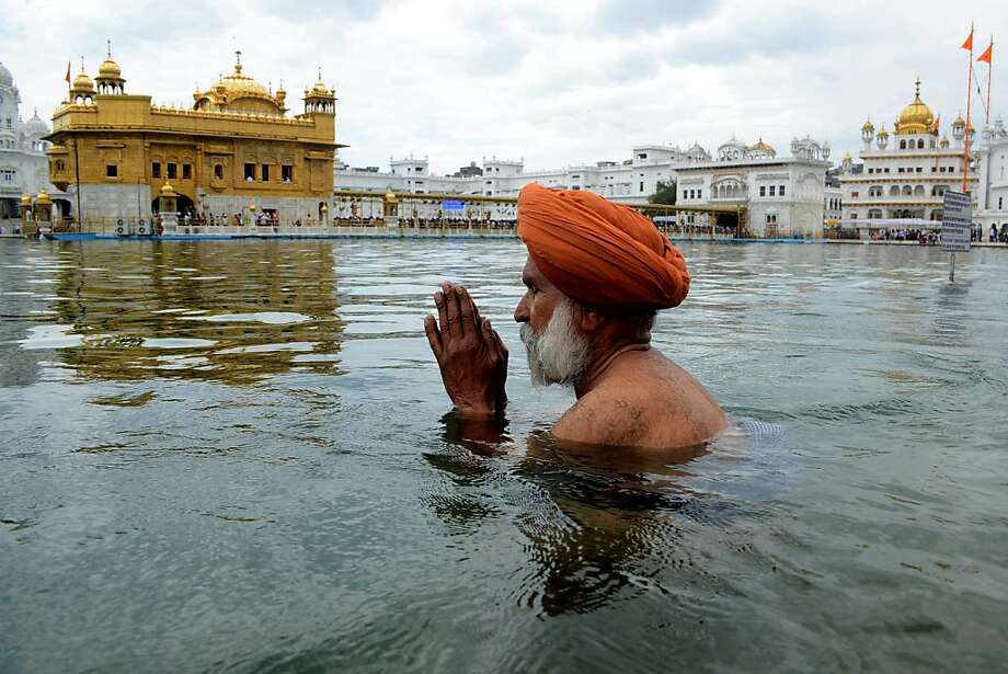An Indian Sikh devotee bathes in the holy  sarover (water tank) on the occasion of 'Hola Mohalla' at The Golden Temple in Amritsar on March 28, 2012. Hola Mohalla is a three day Sikh festival, in which Nihang Sikh 'warriors' perform Gatka (mock encounters with real weapons), tent pegging and bareback horse-riding, which usually falls in March following the Hindu festival of Holi. AFP PHOTO / NARINDER NANUNARINDER NANU/AFP/Getty Images Photo: Narinder Nanu, AFP/Getty Images