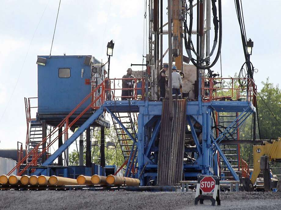 "A crew works a rig using the method known as hydraulic fracturing or ""fracking"" to extract oil and  gas in Zelienople, Pa. Photo: Keith Srakocic, Associated Press"