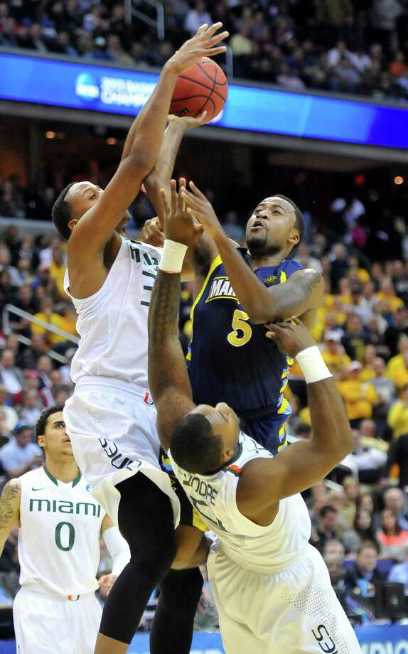 Marquette guard Junior Cadougan (5) puts up a shot against Miami forward Kenny Kadji (35), left, and Miami forward Erik Swoope (21) in the first half of an NCAA Tournament East Regional semifinal at the Verizon Center in Washington, D.C., Thursday, March 28, 2013. (Mark Gail/MCT) Photo: Mark Gail, McClatchy-Tribune News Service / MCT