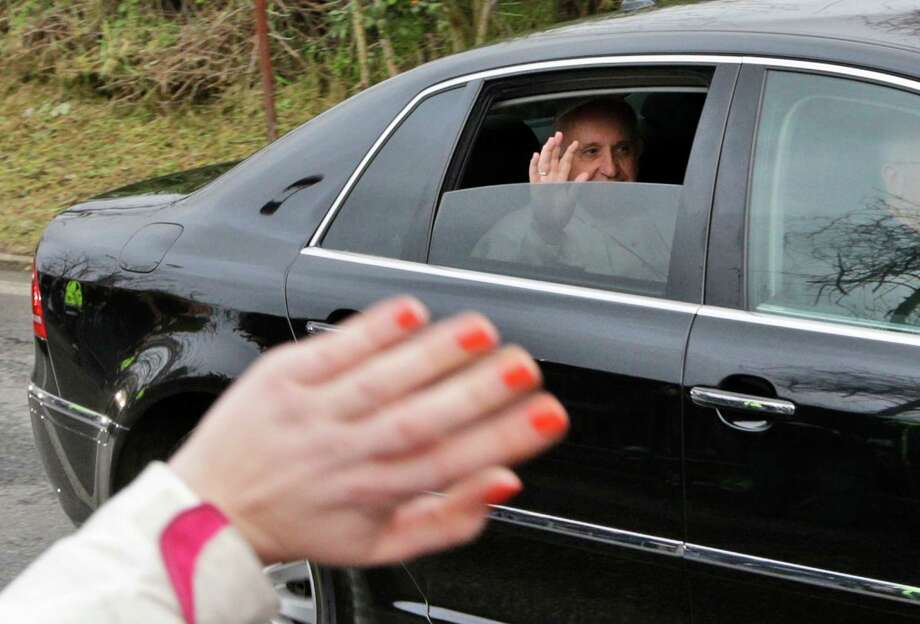 Pope Francis waves from his car as he arrives at the juvenile detention center of Casal del Marmo to celebrate the rite of the washing of the feet, in Rome, Thursday, March 28, 2013. Previous popes have celebrated the Holy Thursday ritual, which re-enacts Christ's washing his disciples feet before being crucified, but they have done so washing the feet of priests in one of Rome's most ornate basilicas, St. Peter's Basilica, not a jail. (AP Photo/Andrew Medichini) Photo: Andrew Medichini, STF / AP
