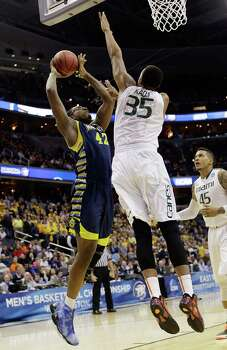 Marquette center Chris Otule (42) shoots over Miami forward Kenny Kadji (35) during the first half of an East Regional semifinal in the NCAA college basketball tournament, Thursday, March 28, 2013, in Washington. (AP Photo/Pablo Martinez Monsivais) Photo: Pablo Martinez Monsivais, Associated Press / AP